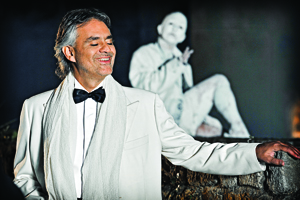 Andrea Bocelli standing with in hand on a stone wall in a white tux.
