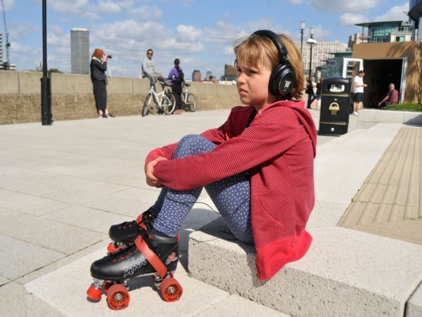 Girl in skates with headphones.