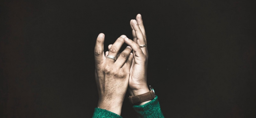 Hands facing upward against black background