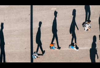 Aerial view of long shadows and people walking