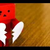 Red toy robot holding broken heart