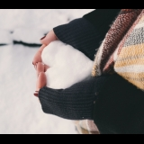 Hands holding heart-shaped block of snow