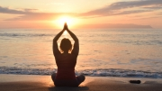 woman in lotus position on beach facing sunset