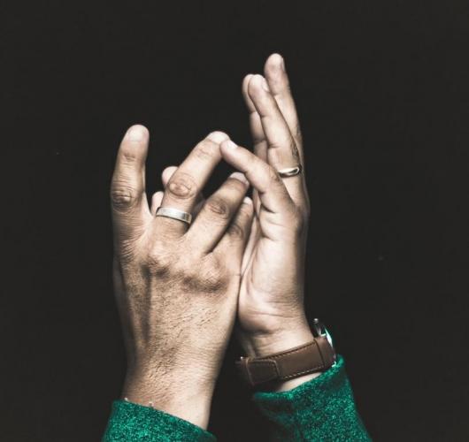 Hands facing upward against black background