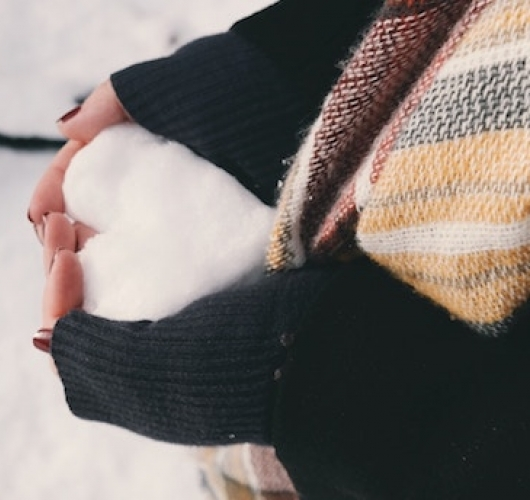 Hands holding snow hear