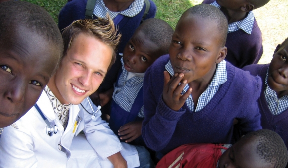 Dr. Ikali with Kenyan school children after health check ups