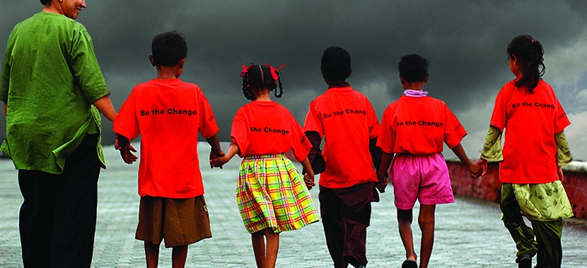 "Rear image of 5 children and one teacher hold hands in a line. Kids wear shirts that say ""be the change"" on the back"