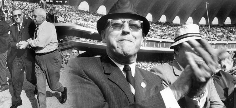 A photo of John E. Fetzer in a suit, sunglasses and hat at a Detroit Tigers game.