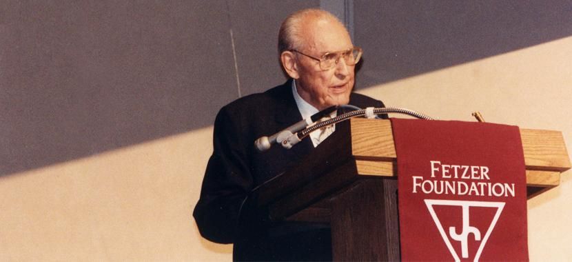 An older John E. Fetzer gives a Keynote speech, standing behind a podium.