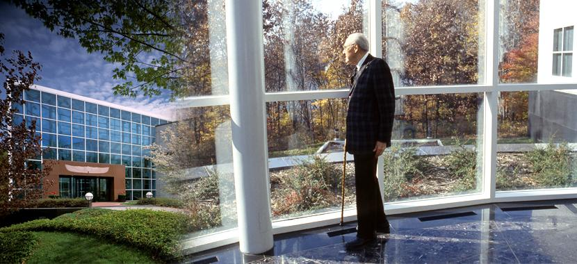 An older John Fetzer standing in front of large glass windows.
