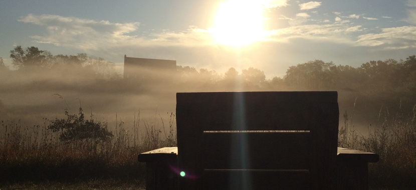 wooden chair on hilltop at sunrise