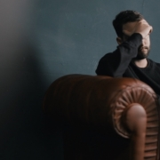 Man with head in hand on a couch