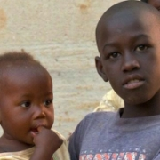 In Uganda, a baby girl is being held by a young boy with a young girl in the background.