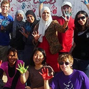 two rows of a diverse group of young people wave with painted hands, a result of creating the banner hanging behind them
