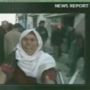 screen shot of news report in the Middle East, a young man pleas before a camera in a scene of the aftermath of violence