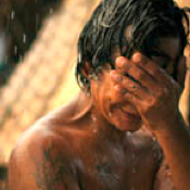 a shirtless man weeps in the rain, covering his face with his hand