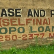 person walking bicycle past SELFINA micofinancing sign painted on concrete wall