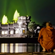 Night scene: Buddhist monks crouch at water's edge, Angkor Watt in background