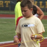 visually impaired boy practices running holding a ring that guides him along a roped path