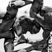 Two Sudanese men wrestle outdoors surrounded by spectators